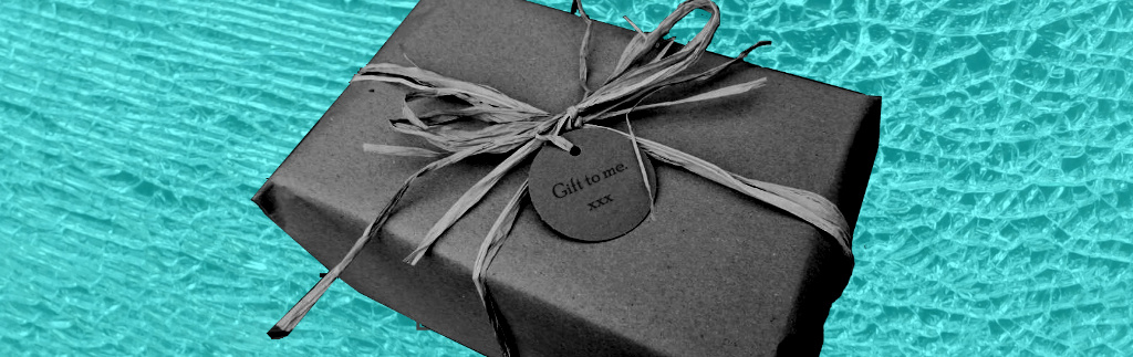"Black and white wrapped gift with label reading ""Gift to me xxx"" on cracked glass background"