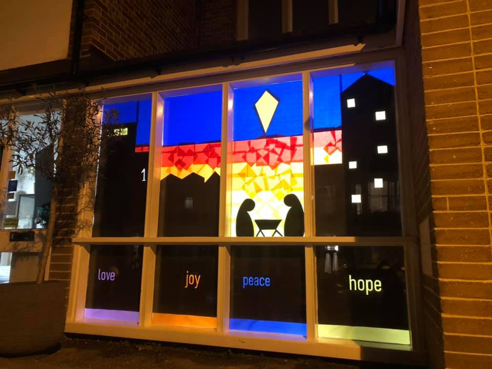 Window with words love, joy, peace and hope in the silhouette of London tower blocks and the simple nativity scene